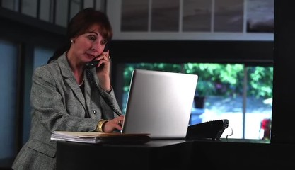 Businesswoman in creative space typing on laptop and answering phone