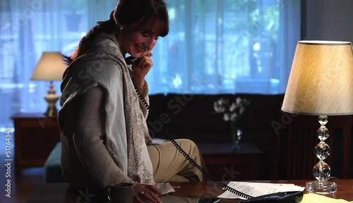 Stylish woman at home talking on telephone and checking digital tablet
