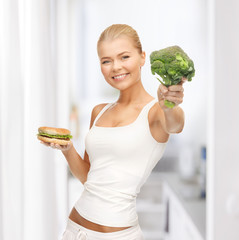woman with broccoli and hamburger