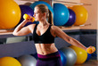sports blonde woman performs exercises with dumbbells in the gym