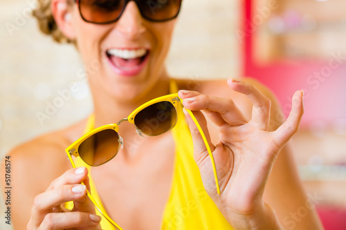 Young woman at optician with sunglasses