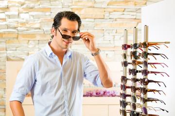 Young man at optician buying sun glasses