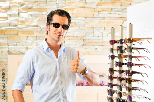 Young man at optician buying sun glasses