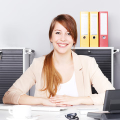 Female office assistant is satisfied with her job