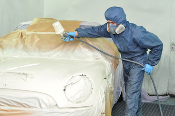 Worker painting car.