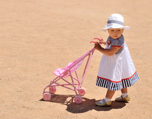 cute baby girl with toy stroller