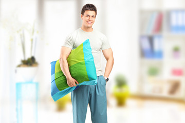 Smiling man in pajamas holding a pillow at home