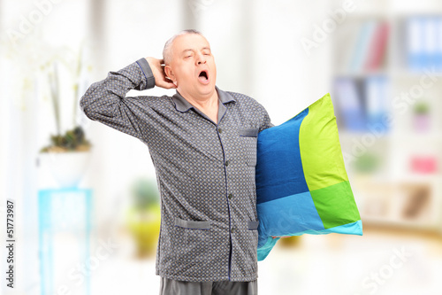 Sleepy mature man in pajamas holding a pillow and yawning at hom