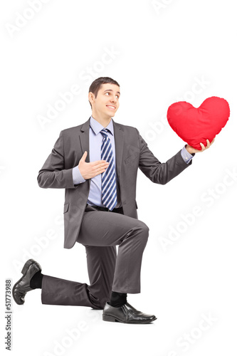 A smiling male in a suit kneeling with red heart