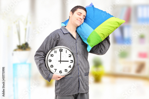 Young lazy guy holding a clock and sleeping on a pillow at home