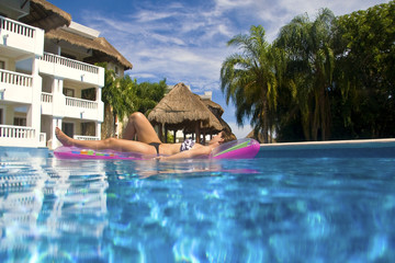 Beautiful girl resting in a swimming pool of a vacation resort