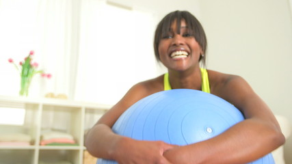 Happy and healthy black woman smiling on exercise ball