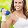 Woman Exercising With Dumbbell...