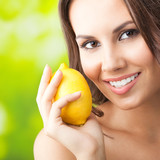 Young happy smiling woman with lemon, outdoors