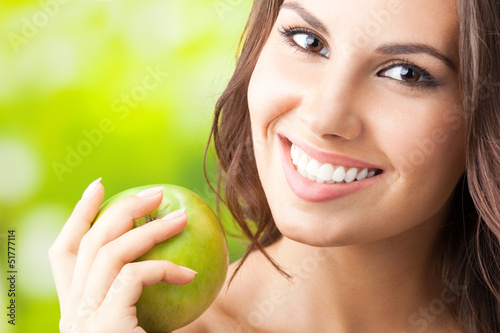Young happy smiling woman with apple, outdoors