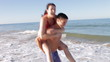Man Giving Woman Piggyback As They Run Along Beach