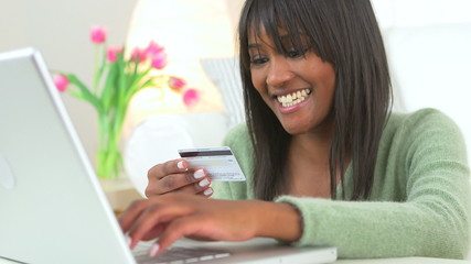 Black woman shopping online with laptop