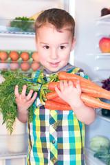 Kleinkind holt Möhren auf dem Kühlschrank