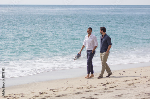 Couple of handsome friends, walking in  a seaside