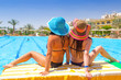 Relax of two tanned girls at swimming pool