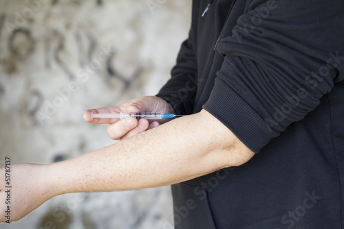 Drug addict with syringe near the hand