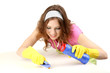 Young housewife cleaning up table at home on grey background