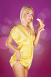 Cute blond woman holding a banana ready to eat over pink backgro