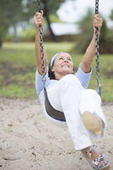 Joyful senior woman on swing active retirement