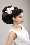 Charisma. Woman with Futuristic Hairstyle and Orchid Flowers