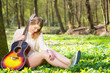 Beautiful blond woman relaxing with guitar under tree