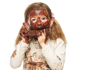 Little girl eating chocolate bar and face covered in chocolate