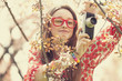 Teen girl in glasses with vintage camera near blossom tree