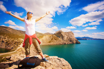 woman tourist is enjoying landscape with outstretched arms