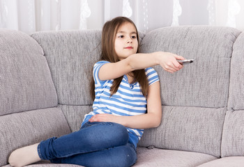 Cute little girl  watching tv on sofa