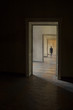 Silhouette in a corridor in front of a closed door.
