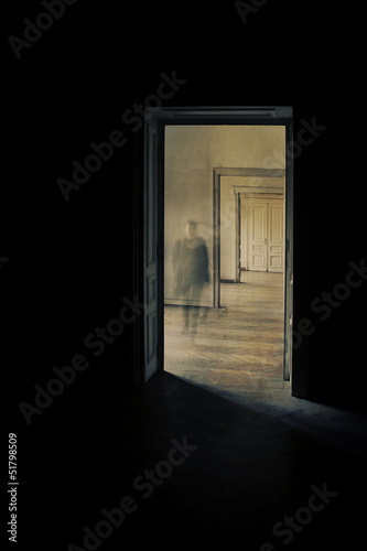 Silhouette in a corridor approaching, closed door behind