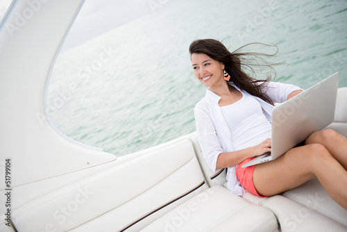 Woman sailing on a yacht with a laptop