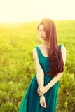 Morning portrait of beautiful girl in green field