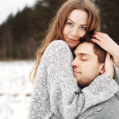 Outdoor happy couple in love posing in cold winter weather