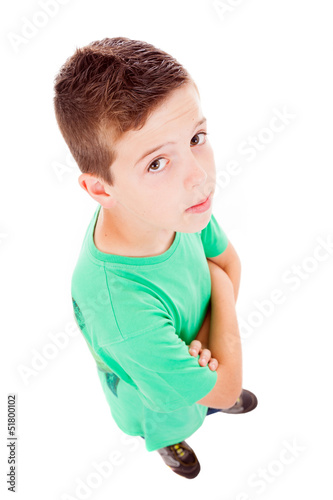 Full body portrait of a little boy looking up against white back