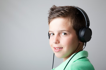 Handsome teen boy listening to music on headphones over grey bac