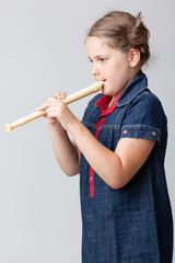 Image of schoolgirl playing the flute on a grey background
