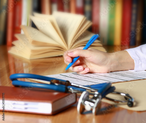 Close-up of writing doctor's hands on a wooden desk