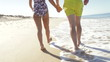 Close Up Of Senior Couple Holding Hands Walking Along Beach