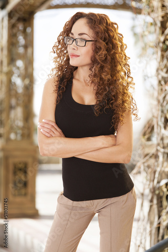 Smart looking woman with glasses smiles as she looks into the di