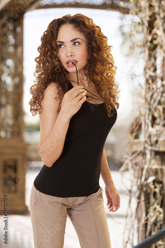 Woman with thick, curly hair looks to the side with glasses on h