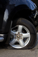 Side of the wheel, flat tire deflated because of an accident