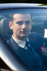 Handsome young groom in a car