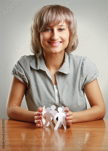 Young woman caring about chain of paper people