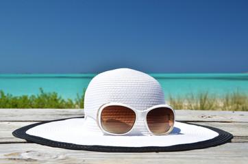Hat and sunglasses on the beach of Exuma, Bahamas